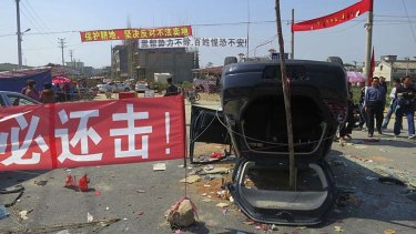 A sign proclaiming 'We must retaliate' is displayed next to an overturned car at the entrance of Shangpu village in China's Guangdong province.