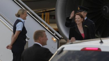Prime Minister Julia Gillard is all smiles as she returns to Canberra from India.