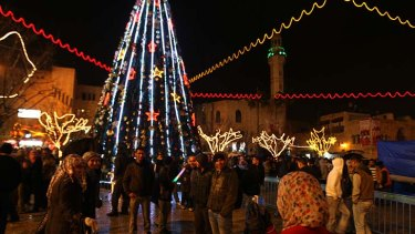 A Palestinian Muslim woman takes pictures in Manger Square, the central plaza next to the Church of the Nativity.