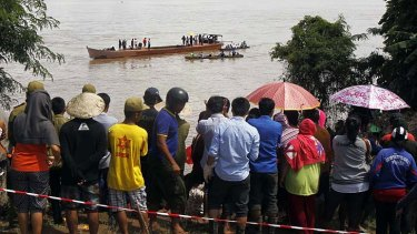 Villagers gather on the banks of Mekong river as rescue personnel on boats search the plane crash site.