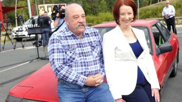 Prime Minister Julia Gillard sits on the boonet of a 1987 Celica with owner Colin Foot at Beenleigh south of Brisbane at the weekend as she announced her 'cash for clunkers' policy.