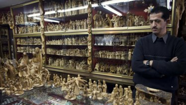 A Palestinian sells olive wood nativity scenes in his shop in Bethlehem.