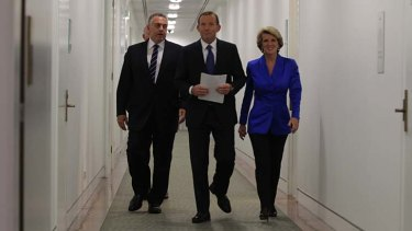 The frontrunner: Tony Abbott, flanked by Joe Hockey and Julie Bishop, sets out to deliver his budget reply on Thursday.