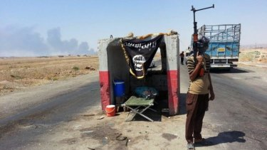 A militant of the Islamic State in Iraq and the Levant (ISIL) stands guard at a checkpoint captured from the Iraqi army outside the Baiji oil refinery.