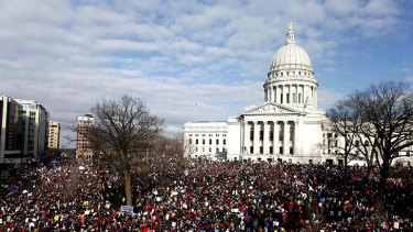 Demonstrators at Wisconsin's State Capitol in Madison join 14 senators who left the state to protest a labour bill that curbs collective bargaining for public workers.