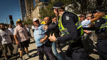 Taxi drivers are seen remonstrating with police during a protest outside State Parliament