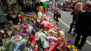 Thousands of people walk along Sydney Road in a peace march after the murder of Jill Meagher. Flowers left at the Duchess Boutique where Jill was caught on CCTV.