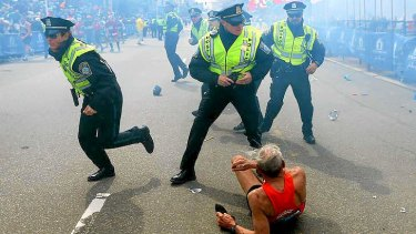 Bill Iffrig, 78, lies on the ground as police officers react to a second explosion at the finish line of the Boston Marathon.