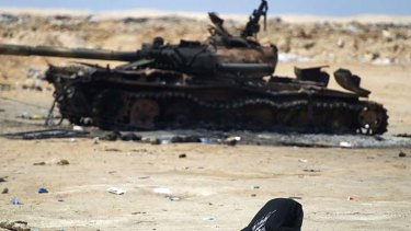 A Libyan rebel at prayer in front of a burnt-out tank.