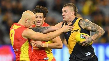 Don't argue: Richmond's Dustin Martin fends off Gold Coast skipper Gary Ablett.
