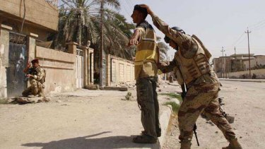 An Iraqi soldier frisks a resident in Basra.