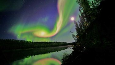 Swirls of green and red appear in an aurora over Whitehorse, Yukon on the night of September 3, 2012, as a result of the eruoption from the Sun.