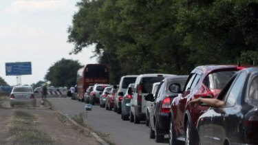 Cars queue at a checkpoint as people flee the southern Ukrainian city of Mariupol amid fears of an attack by pro-Russian militants.