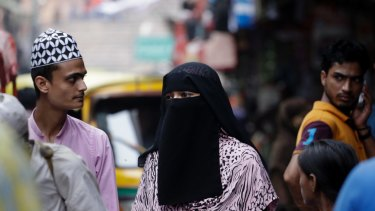 An Indian Muslim woman walks at a market area in Delhi, India.