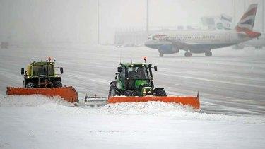 Snow ploughs clean the tarmac at Munich airport.