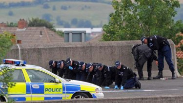 Police officers conduct a fingertip search on the road in Newcastle northern England where a police officer was shot earlier in the day.