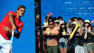 Roger Federer attracts a large gathering for a practice session on the outside courts.