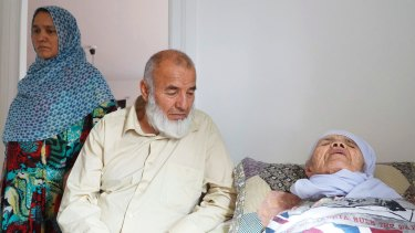 106-year-old Afghan refugee Bibihal Uzbeki rests in bed attended by her son Mohammadollah and daughter-in-law Ziba, in Hova, Sweden.
