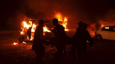 Pakistani volunteers and soldiers carry a blast victim in Quetta, Pakistan, on Saturday.