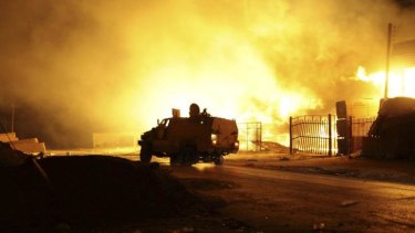 A building burns after clashes in the Sarraj district of the Libyan capital Tripoli.