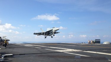 A jet fighter takes off on a US aircraft carrier in the South China Sea.