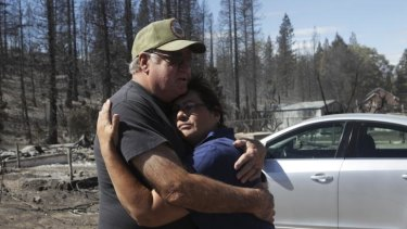 Jim Taylor hugs lifelong friend, Mary Mazzoni, in in Weed, California. Taylor's home was one of three on his street that survived the Boles Fire.