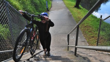 Missing link: A cyclist carries her bike up stairs on the Yarra Trail in Abbotsford.