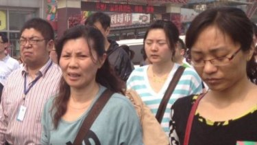 Liu Fenghua (3rd from right), mother of a missing MH370 passenger, marches with other relatives to the Malaysian consulate in Beijing.