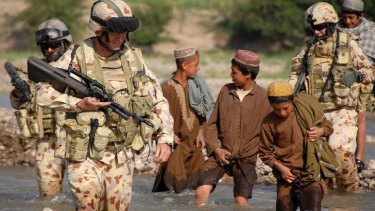 Lieutenant Colonel Stuart Yeaman followed by Afghan boys at a river crossing at Talani, southern Afghanistan.