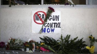 A sign advocating gun control is seen on a makeshift memorial for 20-year-old university student Christopher Michael-Martinez.