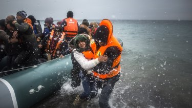 Refugees and migrants disembark on  on the Greek island of Lesbos, after crossing from Turkey.