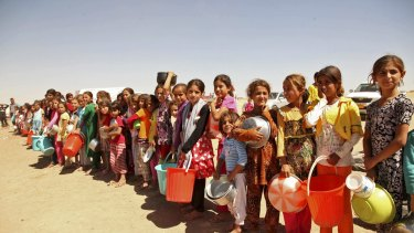 Yazidis fleeing violence in the Iraqi town of Sinjar west of Mosul last year line up for food.