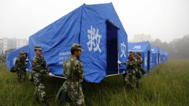 Safe havens: Chinese paramilitary policemen set up tents for quake victims on the grounds of a primary school in Yongping.