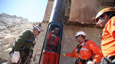 Rescuers test a capsule similiar to the one that will be used to liberate the trapped miners.