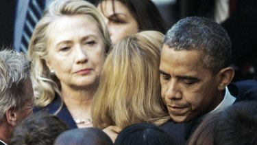 Then US Secretary of State Hillary Clinton looks on as US President Barack Obama hugs a State Department employee on September 12, 2012, a day after  the killing of US Ambassador to Libya Christopher Stevens and three staff members.