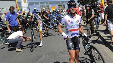 Angry:  Mark Cavendish of Britain walks with his bicycle after he fell off.