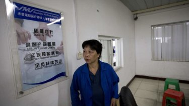Gao Ping, a worker in the alcohol prep pads division, leaves a room after speaking to journalists inside the Specialty Medical Supplies plant, where American Chip Starnes is being held hostage.