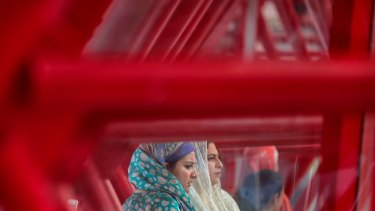 Women watch from a separate section as men take part in Eid al-Adha prayers, held in a sports hall in Bucharest, Romania.