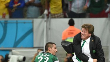 Mexico's coach Miguel Herrera (right) and Mexico's defender Paul Aguilar share a happy moment.