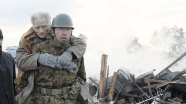 An elderly man is being carried by Self-Defense Force member in the tsunami-torn Natori city.