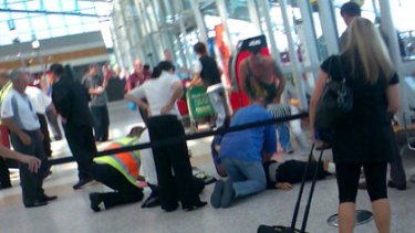 Bystanders with the victim of the attack at Sydney Airport's domestic terminal.
