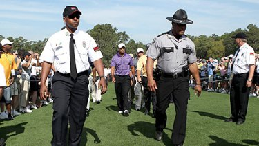 Tight security surrounds Woods as he plays a practice round at Augusta before his comeback tomorrow.