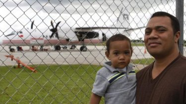 Sau Tongi, holding his son, stands in front of a China-made MA-60 plane. The dispute over the plane represents a small skirmish in a broader battle for global influence.
