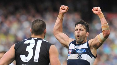Jimmy Bartel raises his arms in triumph after scoring; Chris Dawes finds it too painful to look.