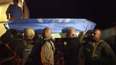 Laid to rest ... UN personnel carry the casket of a colleague killed in an attack on the UN operations centre in Mazar-e-Sharif.