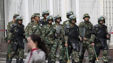 Armed presence: paramilitary policemen patrol near the People's Square in Urumqi, the capital of Xinjiang.