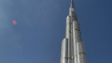 Emirati men walk past Burj Dubai, the world's tallest tower, in the Gulf emirate nation.  In an ambitious move, US department Bloomingdale's has opened in the tower.