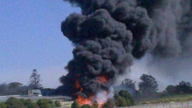 Thick smoke pours out of the burning honey factory at Richmond in southwest Brisbane.