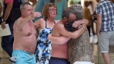 Tourists console each other following a shooting attack in the Tunisia resort town of Sousse.