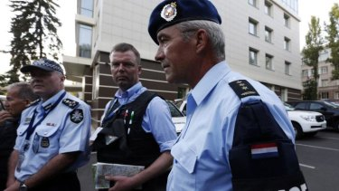 Head of Australian Federal Police mission Commander Brian McDonald (left), OSCE's Alexander Hug (centre), and a Dutch police officer arrive back from the MH17 site on Thursday.